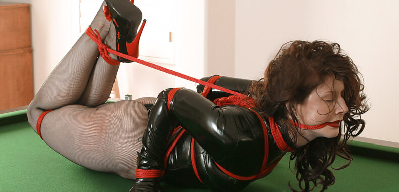 Tied up bondage girl with high heels, red rope and shiny clothes